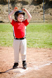 Child playing baseball. Child celebrates on base after making a hit during baseball game Stock Photo