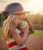 Child Playing Baseball Game on Field. A little child is playing a game of baseball on the dirt field with a glove mitt on for a sport or recreation concept Royalty Free Stock Photography