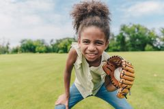 Child playing baseball in park. Portrait of smiling african american little girl with baseball glove and ball playing baseball in park Royalty Free Stock Image