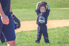 Child Playing Baseball. Young boy standing in baseball field waiting for action Royalty Free Stock Photo