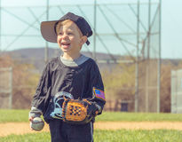 Child Playing Baseball. Young boy standing in baseball field waiting for action Royalty Free Stock Images