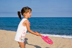 Child playing on the beach. Child playing rackets on the beach stock photography