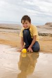 Child playing on beach Stock Photos
