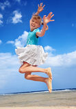 Child playing on beach aganiist blue sky. Stock Image