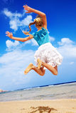 Child playing on beach aganist blue sky. Royalty Free Stock Images