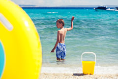 Child playing on beach with colorful toys. Royalty Free Stock Images