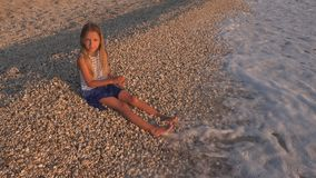 Child Playing on Beach, Kid at Sunset, Girl Throwing Pebbles in Sea Water royalty free stock photography