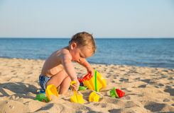 Child playing on the beach. Little boy playing with sand at the beach in summer stock photos