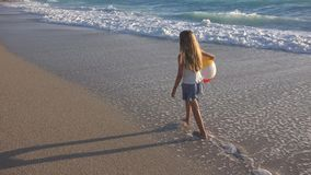 Child Playing on Beach at Sunset, Happy Kid Walking in Sea Waves Girl on Seaside.  stock image