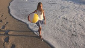 Child Playing on Beach at Sunset, Happy Kid Walking in Sea Waves Girl on Seaside royalty free stock photo