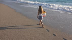 Child Playing on Beach at Sunset, Happy Kid Walking in Sea Waves Girl on Seaside royalty free stock image