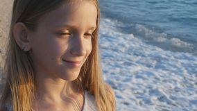 Child playing on beach in sunset, kid watching sea waves, girl portrait on shore stock footage