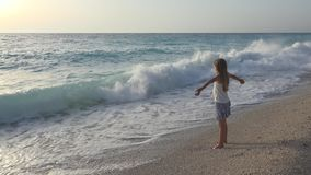 Child Playing on Beach in Sunset, Kid Watching Sea Waves, Girl View at Sundown.  royalty free stock photo