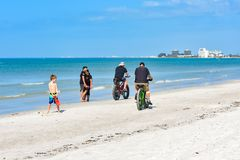 Child playing on the beach watching people ride a bicycle royalty free stock image