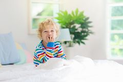 Child playing in bed. Kids room. Baby boy at home royalty free stock images