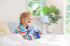 Child playing in bed. Kids room. Baby boy at home stock photography