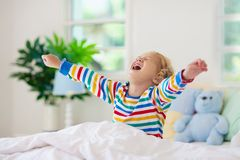 Child playing in bed. Kids room. Baby boy at home. Child playing in bed in white sunny bedroom with window. Kids room and interior design. Baby boy at home royalty free stock photos
