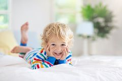Child playing in bed. Kids room. Baby boy at home royalty free stock image