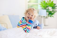 Child playing in bed. Kids room. Baby boy at home stock photos