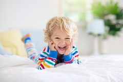 Child playing in bed. Kids room. Baby boy at home royalty free stock photos