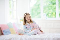 Child playing in bed. Kids room. Girl at home stock photos