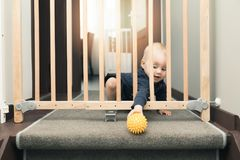 Child playing behind safety gates in front of stairs. At home Royalty Free Stock Photo