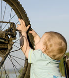Child playing with bike wheel Royalty Free Stock Photography