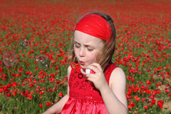 Child playing blowing bubbles. Happy child playing outdoors in summer blowing bubbles Royalty Free Stock Photo