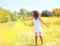 Child playing blowing soap bubbles on meadow Stock Photography