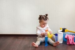 Child playing with bottles with household chemicals sitting on the floor of the house. Child playing with bottles with household chemicals sitting on the floor stock images