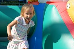 Child playing in bouncy castle. Child playing in color bouncy castle outdoor Royalty Free Stock Image