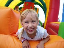 Child playing in bouncy castle. Portrait of a smiling little girl playing in color bouncy castle outdoor Royalty Free Stock Photography