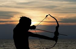 Child playing bow and arrow on the beach, Silhouette royalty free stock photos