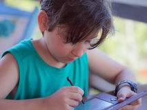 Child playing. Boy writing on the compact videogame with tropical restaurant - Brazil Stock Photo