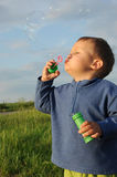 Child playing with bubble gum. Little child, young boy playing wit bubble gum, blowing and making bubbles Royalty Free Stock Image