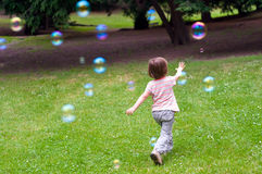 Child playing with bubbles. Little girl catching rainbow soap bubbles in city park Grobovka, Prague, Czech Republic Stock Photos