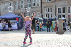 Child playing with bubbles in Bremen - Germany. Child playing with bubbles made by a street bubble-maker in a summer afternoon at the market square in the Royalty Free Stock Image