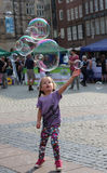 Child playing with bubbles. Made by a street bubble-maker in a summer afternoon at the market square in the historic city centre of Bremen, Germany. Photo taken Royalty Free Stock Photo