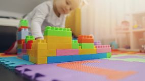 Child playing with building blocks on the floor stock footage