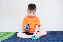 Child playing car game,boy playing with toys sitting on bed indoor,kid holding two toy cars alone Stock Image