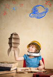 Child playing with cardboard toy rocket. Child astronaut with cardboard toy rocket. Child playing at home. Earth day concept Royalty Free Stock Photo