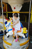 Child playing Carousel horse stock photography