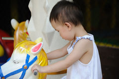 Child playing Carousel horse stock images