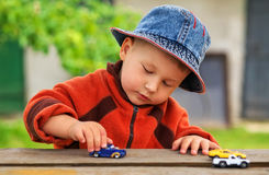 Child playing with the cars close. Royalty Free Stock Images