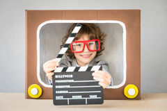 Child playing with cartoon TV. Child playing with cardboard box TV. Kid having fun at home. Communication concept Stock Photo