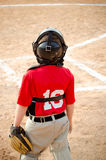 Child playing catcher during baseball game