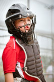 Child playing catcher during baseball game. Portrait of child with catcher equipment on during baseball game Stock Image