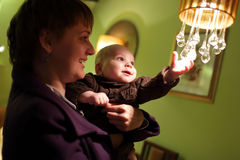 Child playing with chandelier Stock Photos