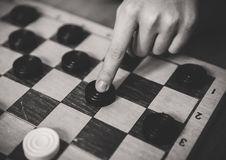 Child playing checkers board game. Black and white royalty free stock photo