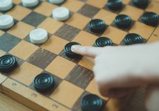 Child playing checkers board game. Close-up view royalty free stock images